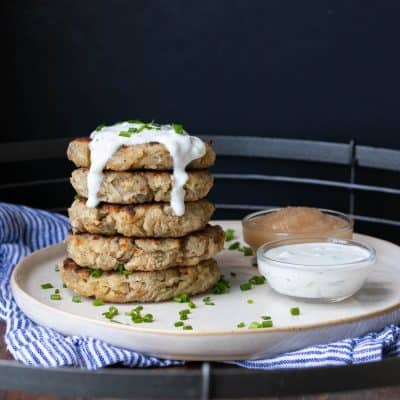 Stack of potato pancakes on a cream plate with dippers next to it