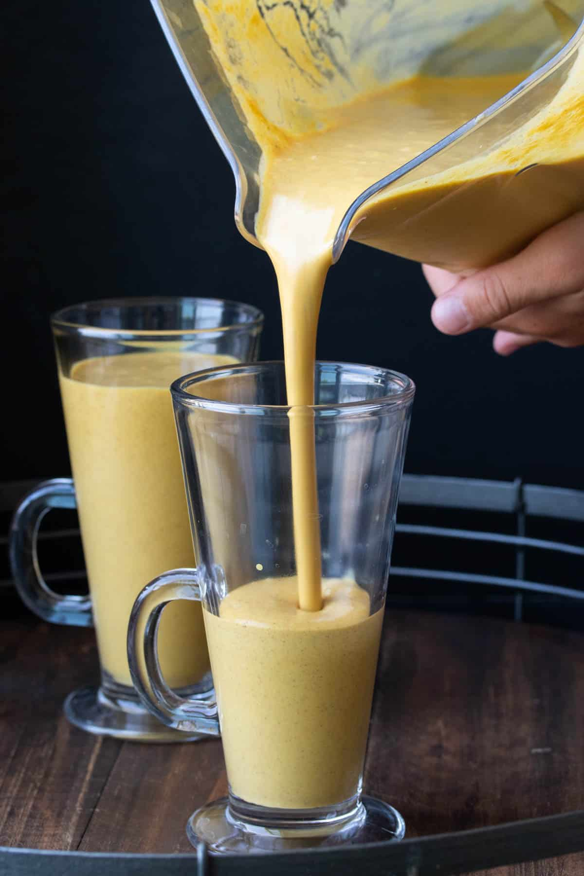 A pumpkin smoothie being poured into a glass jar