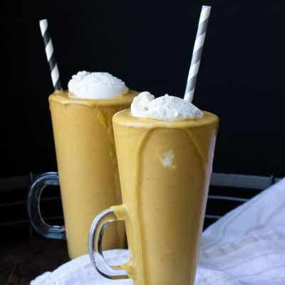Two glass jars with pumpkin pie milkshakes topped with whipped cream