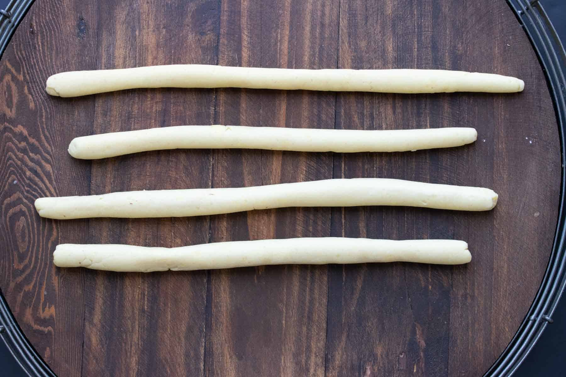 Four rolled out pieces of dough on a wooden surface