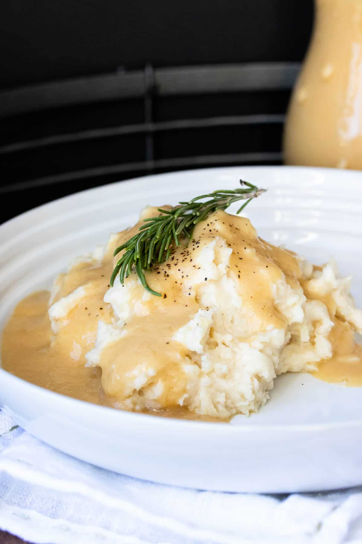 Gravy covered mashed potatoes with a sprig of rosemary on a white plate
