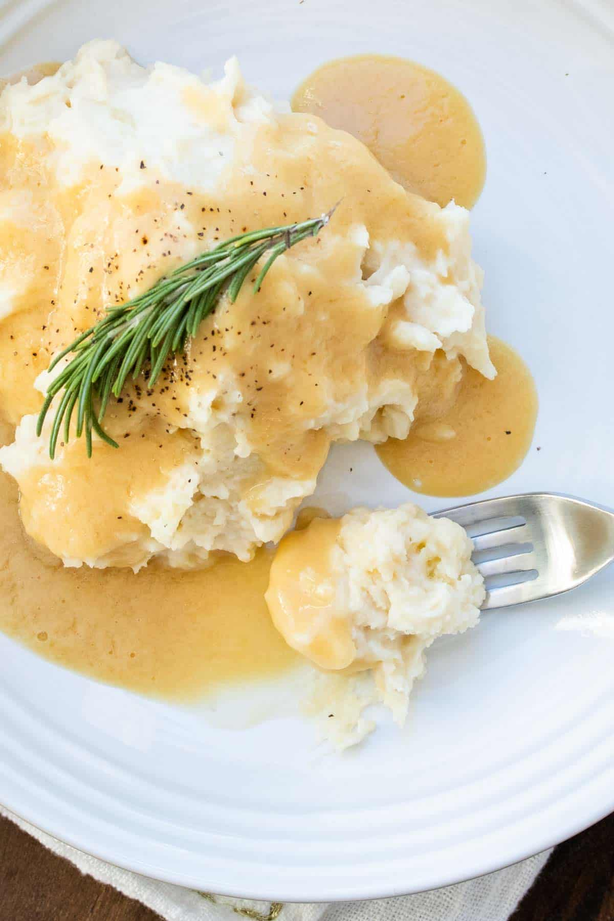 Fork getting a bite of gravy and mashed potatoes