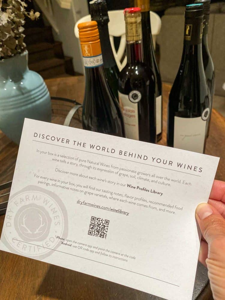 Hand holding an information card on dry farmed wines