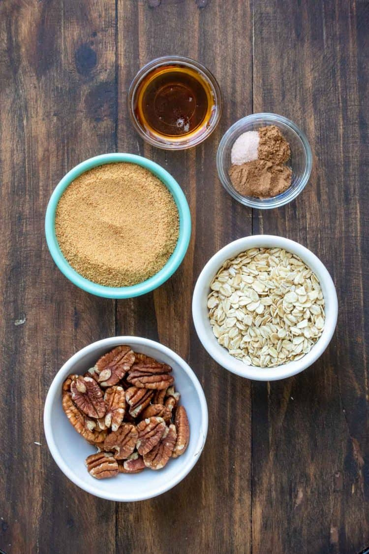 Bowls on a wooden surface filled with ingredients to make a sweet pecan topping