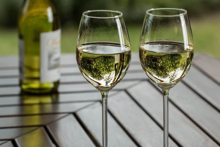 Two wine glasses on a table with white wine in them