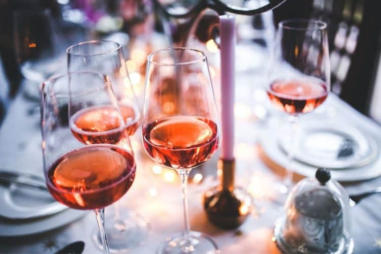 Four glasses on a table filled with rose wine