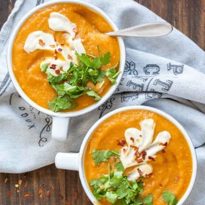 Two white bowls filled with carrot soup and topped with cilantro and cream