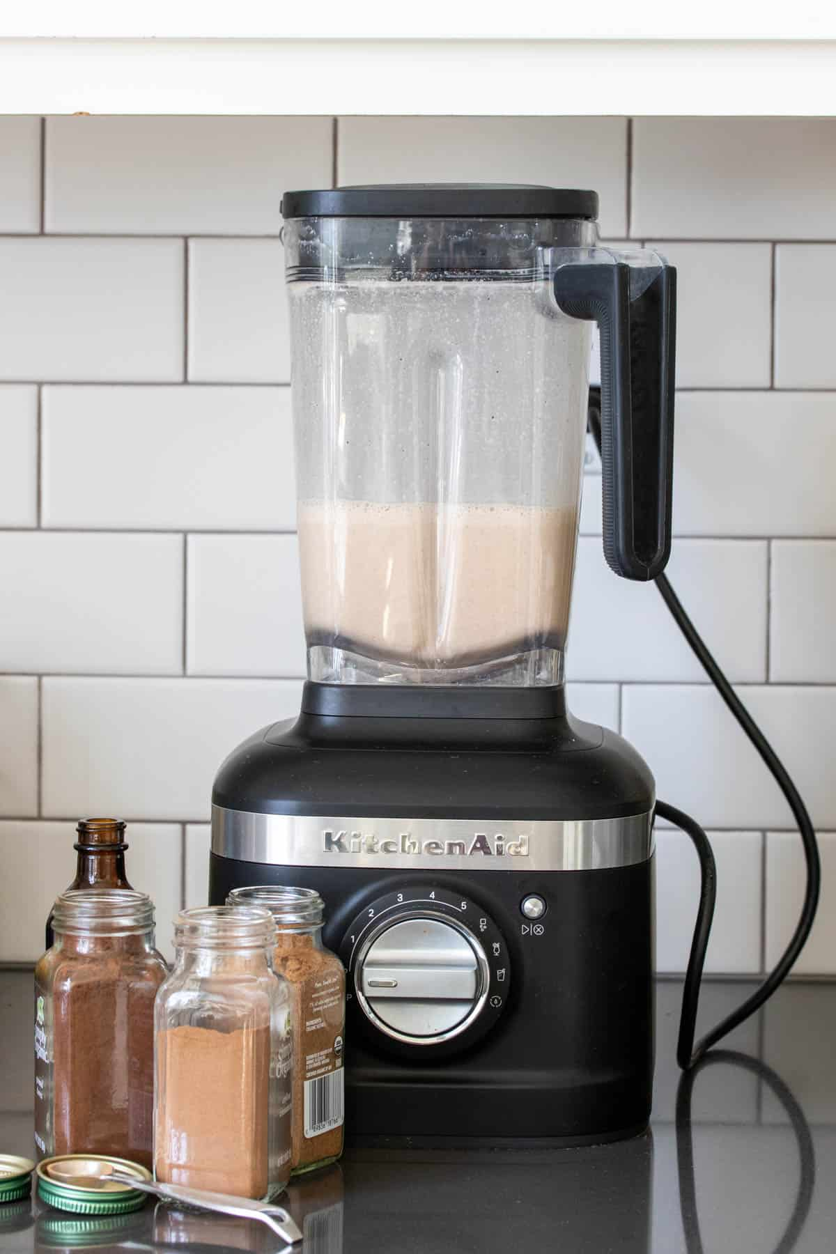 Blender filled with eggnog and with spices in front of it