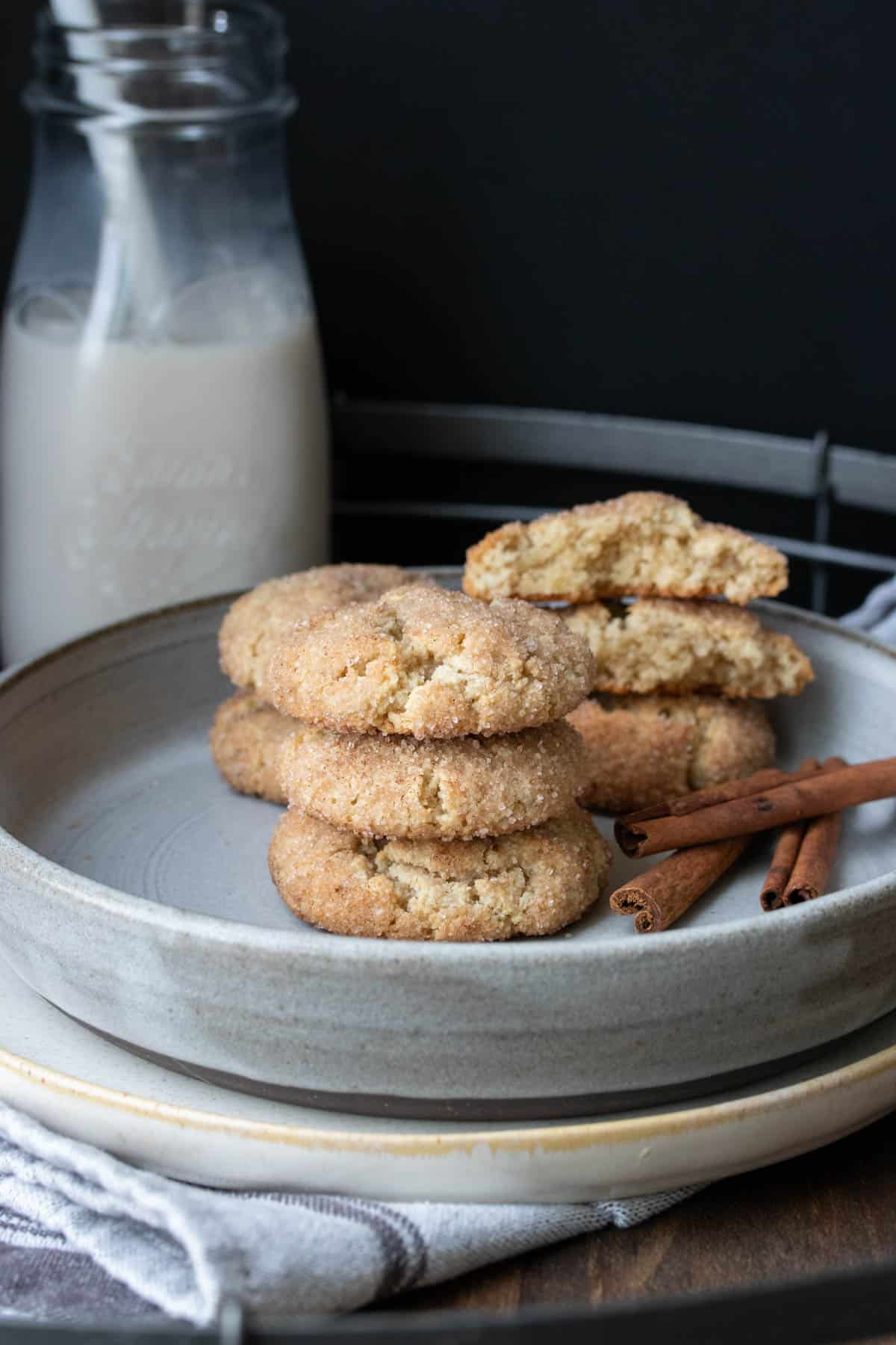 Grey plate with snickerdoodle cookies in front of a glass jar of milk