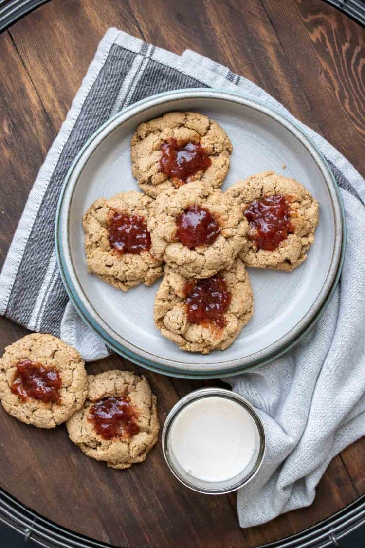 Thumbprint cookies with berry jam on a grey plate on a wooden surface