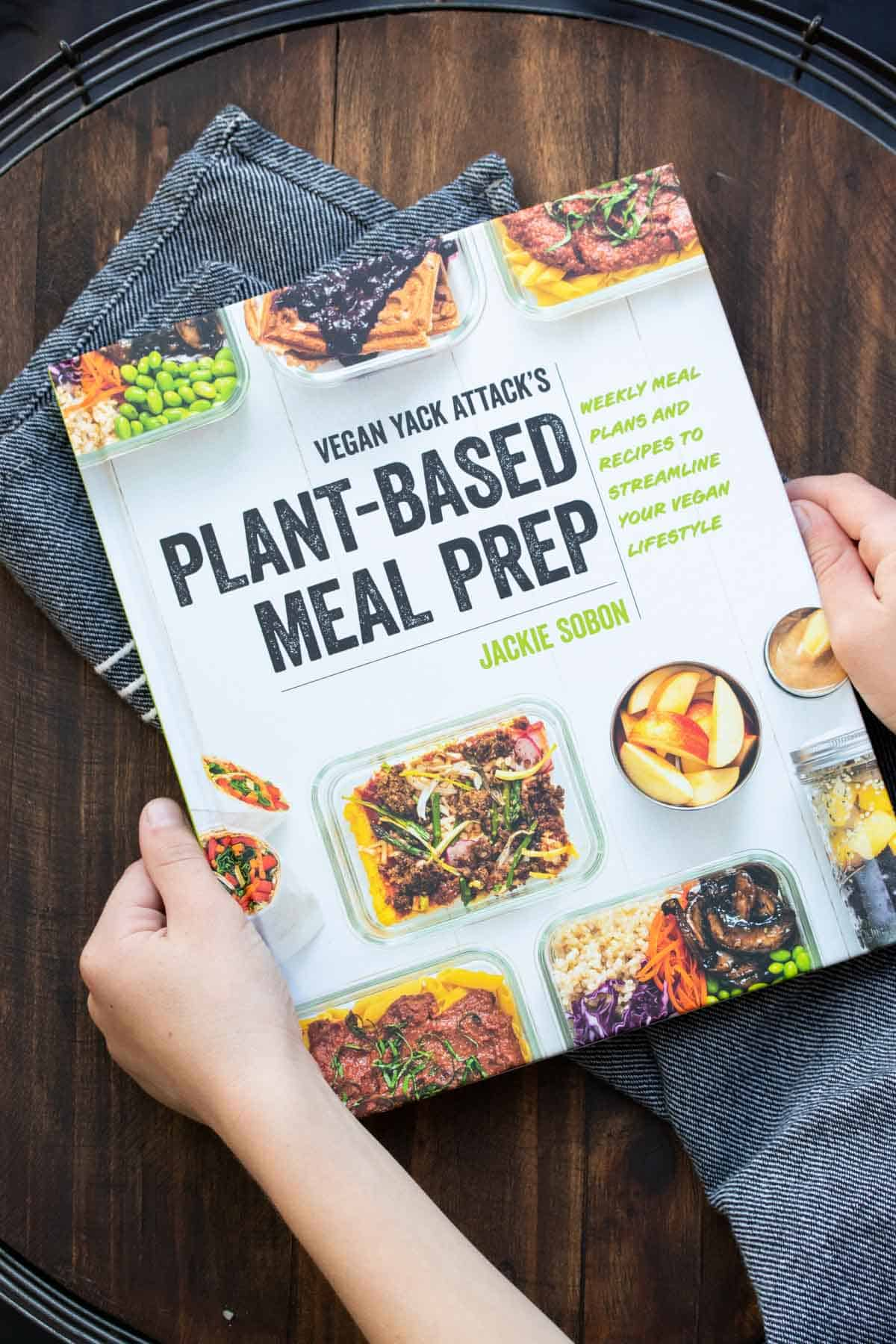 Hands holding a meal prepping cookbook with containers of food on the cover