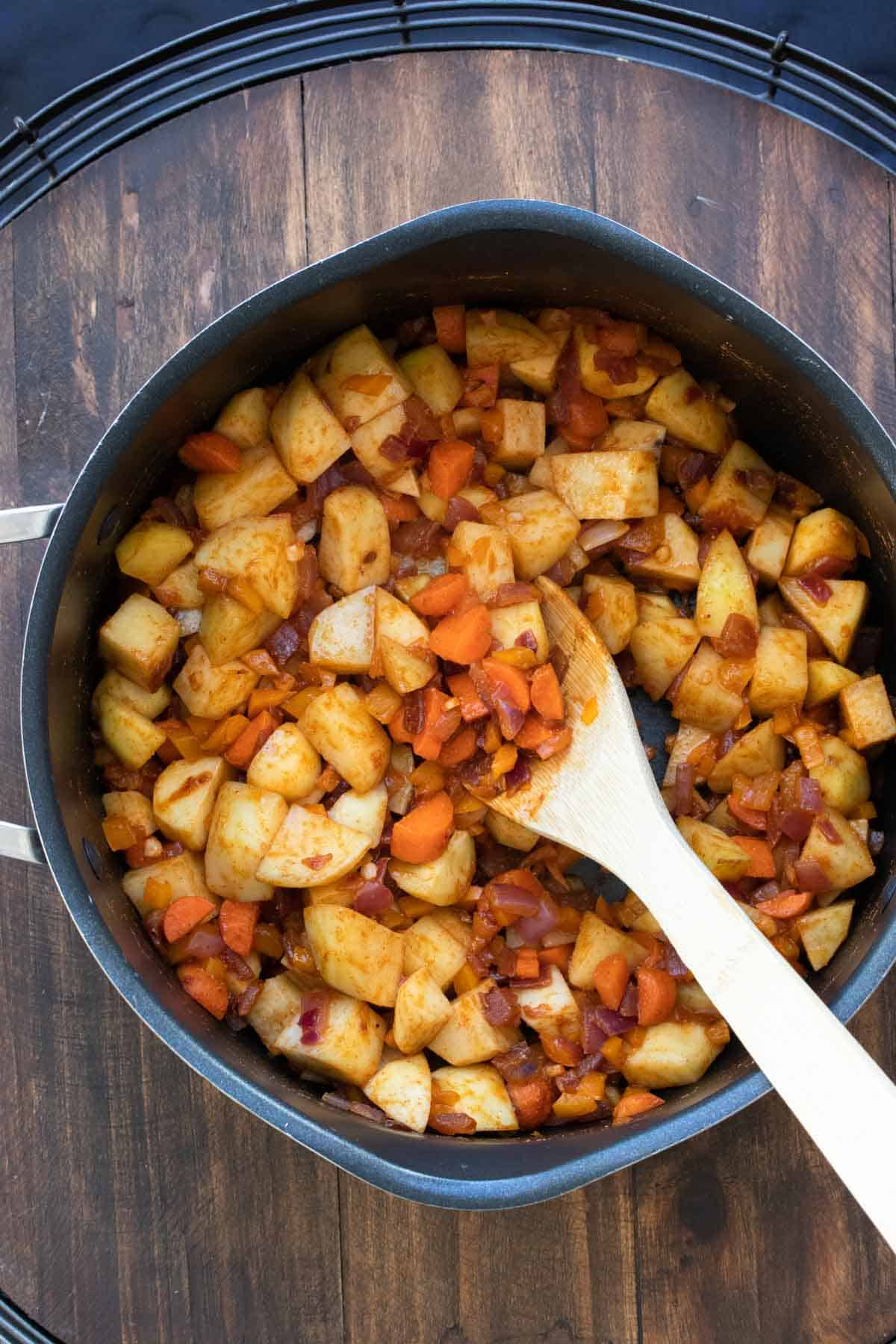 Wooden spoon stirring sweet potatoes, carrots and onion in a pot