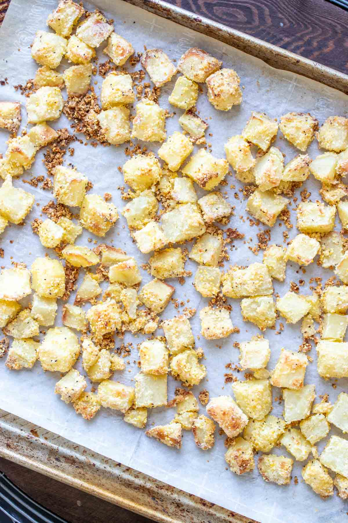 Baking sheet with parchment paper and baked crispy potato pieces