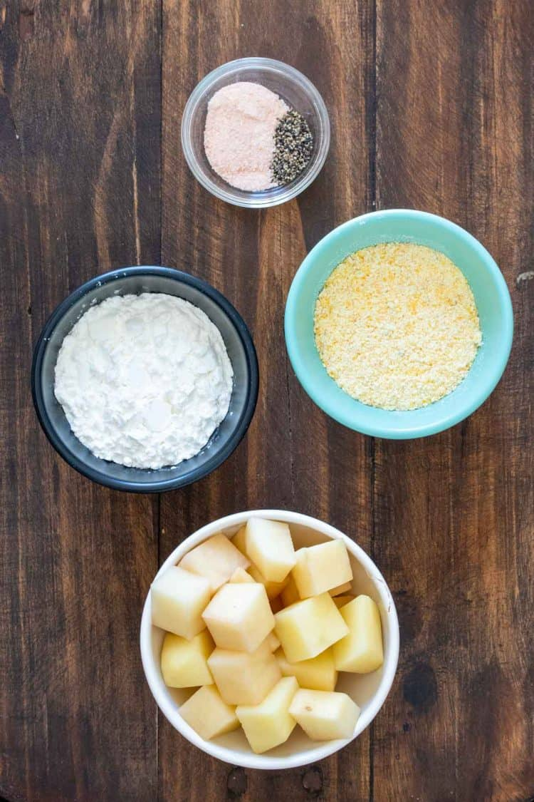 Bowls with cubed potatoes, cornmeal, cornstarch, salt and pepper