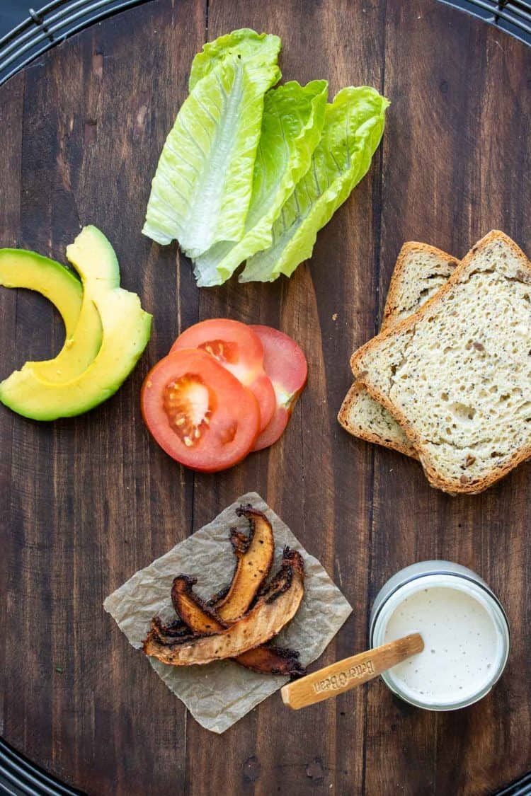Top view of ingredients to make a vegan BLT on a wooden surface