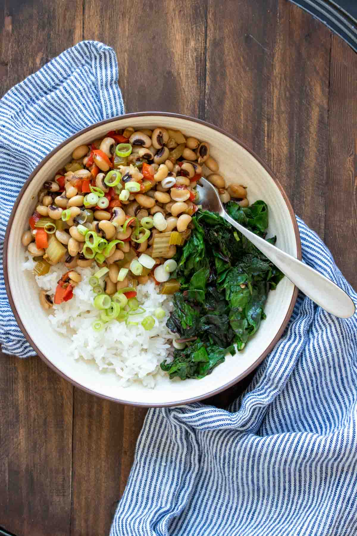Cream bowl filled with rice, black eyed peas and swiss chard