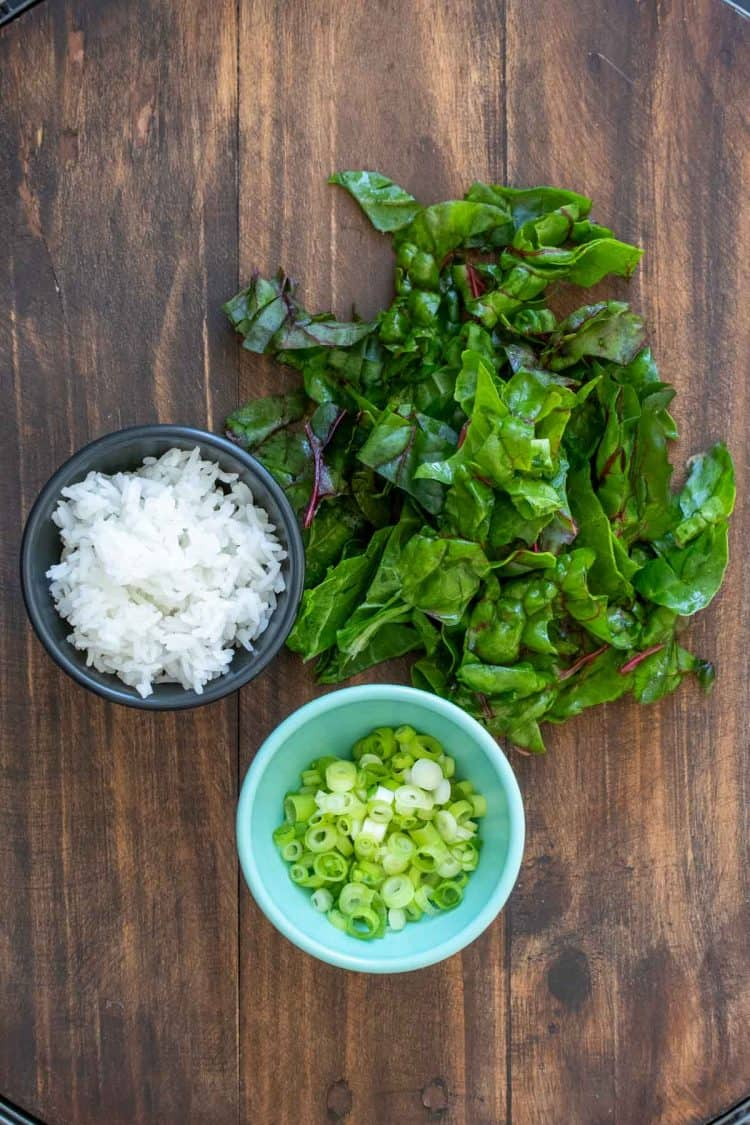 Chard, sliced green onions and rice on a wooden surface