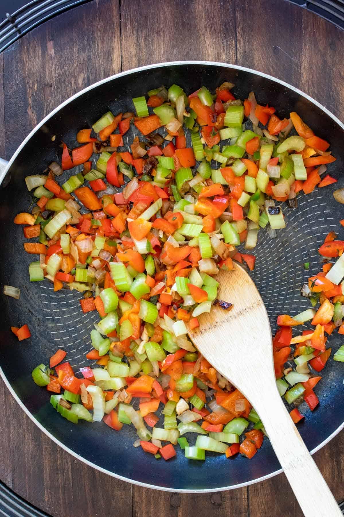 Wooden spoon stirring chopped veggies in a pan