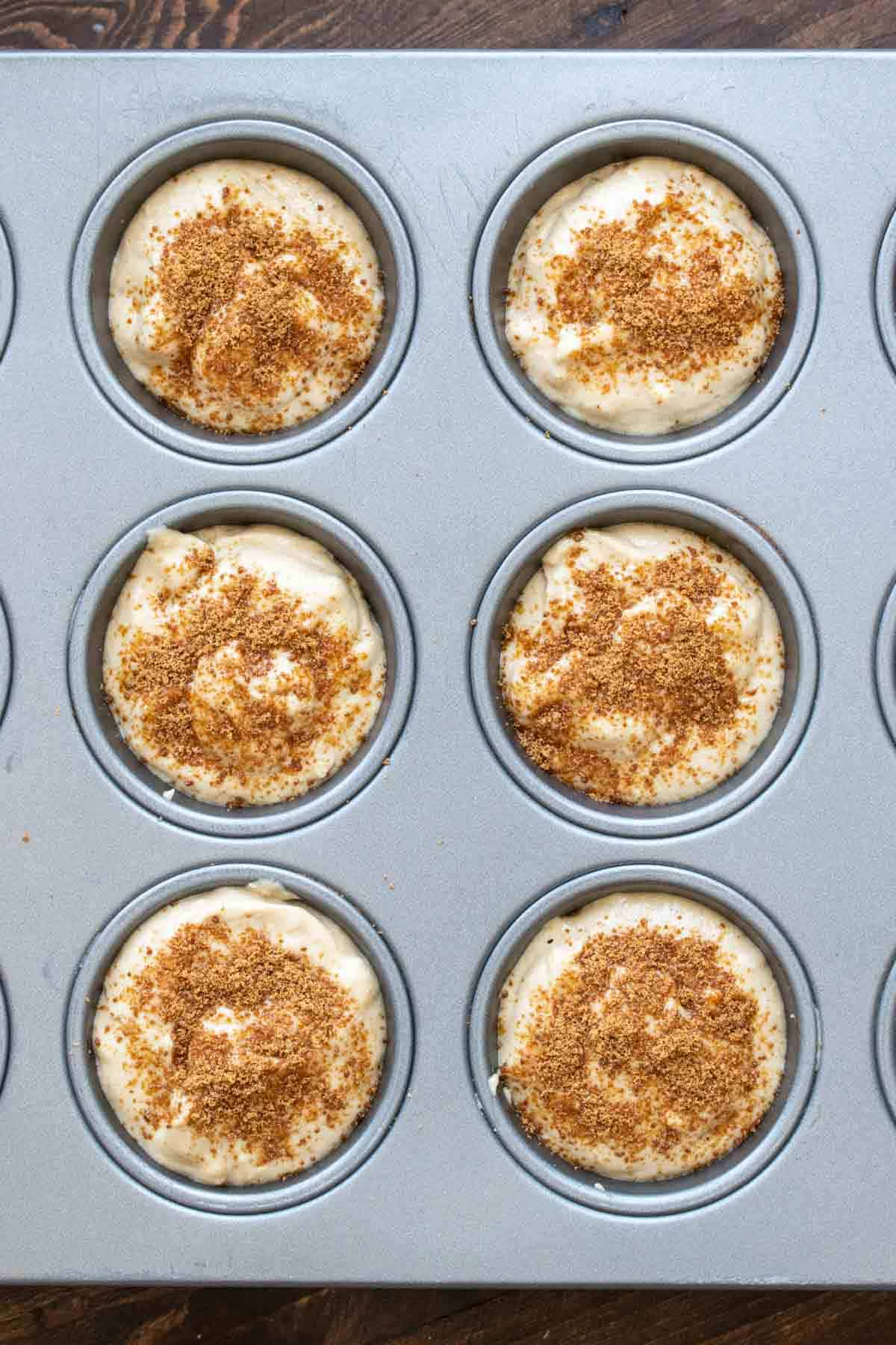 A muffin tin filled with muffin batter sprinkled with coconut sugar