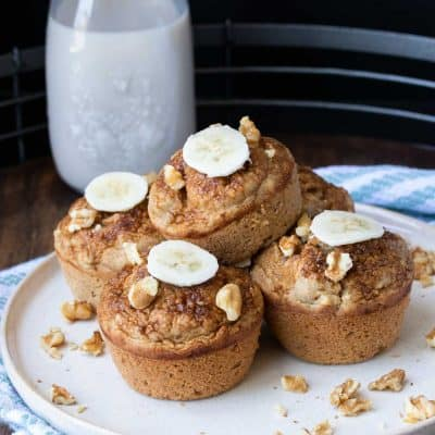 A pile of muffins topped with walnut pieces and banana slices