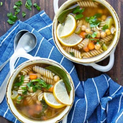 Two white soup bowls filled with chickpea veggie noodle soup