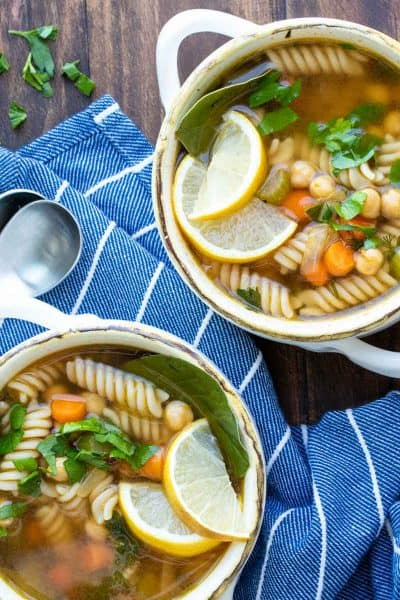 Veggie, chickpea and noodle soup in two soup bowls on a wooden surface