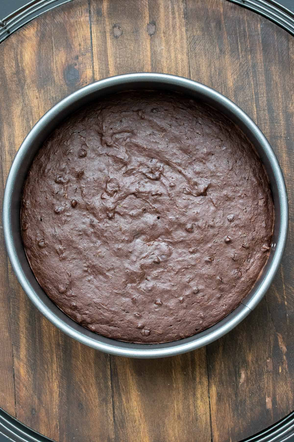A round chocolate cake baked in a pan