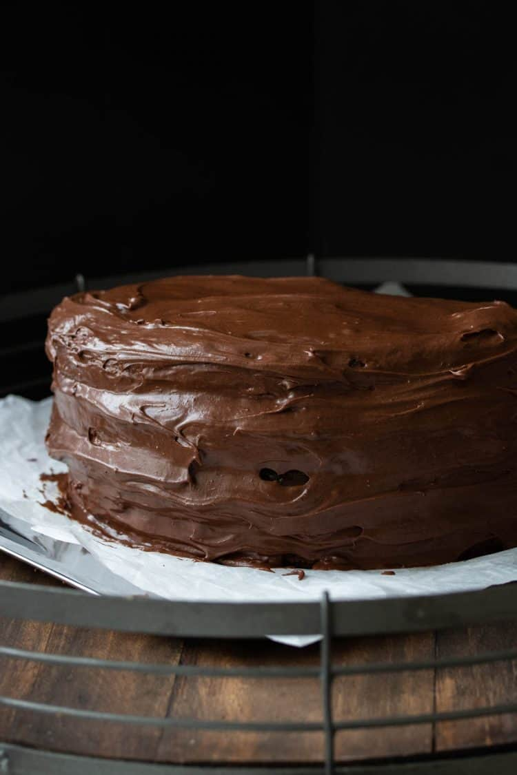 A frosting round chocolate cake on a wooden surface