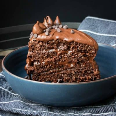 A layered piece of chocolate cake standing up in blue bowl