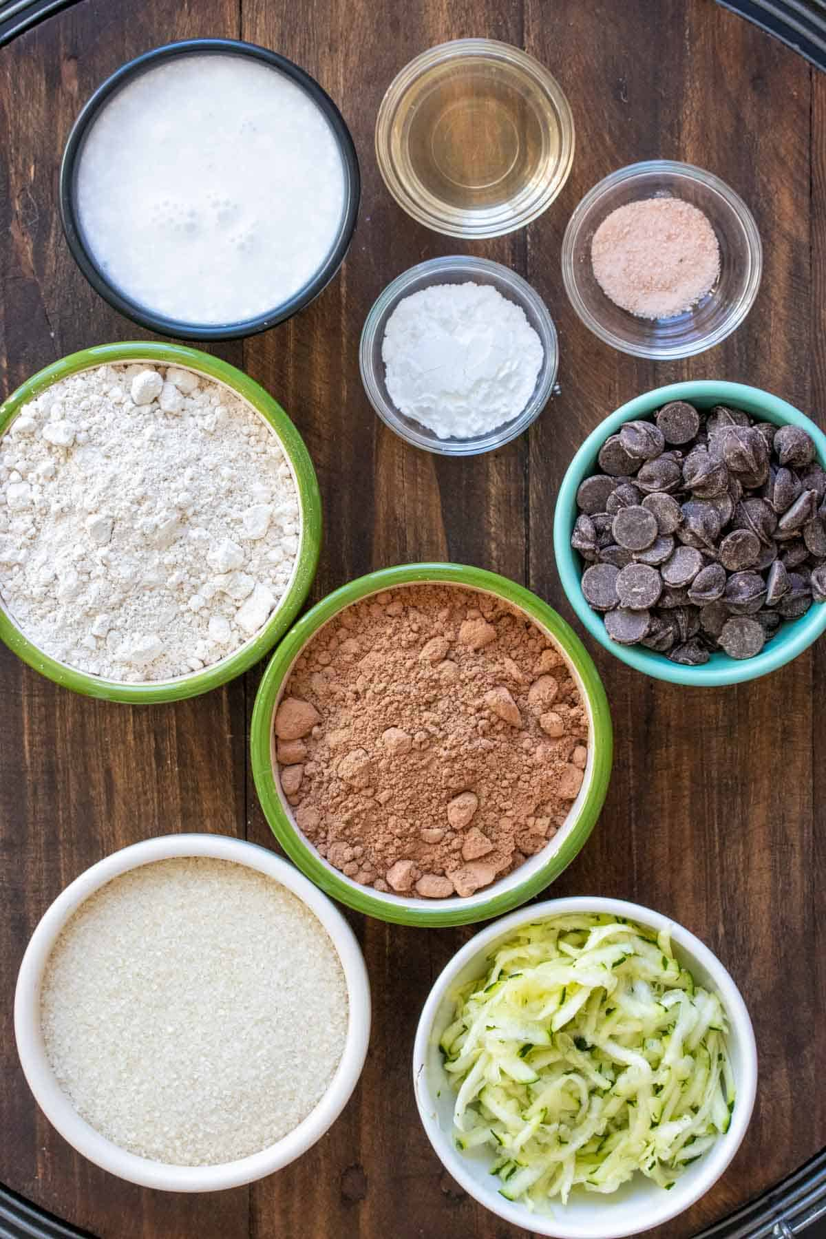Bowls in different colors and sizes with ingredients to make a chocolate zucchini cake