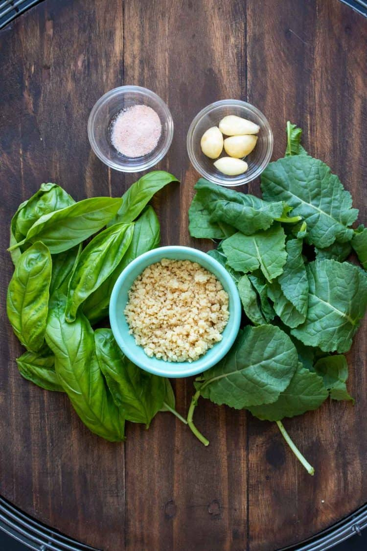 Ingredients needed to make kale pesto on a wooden surface