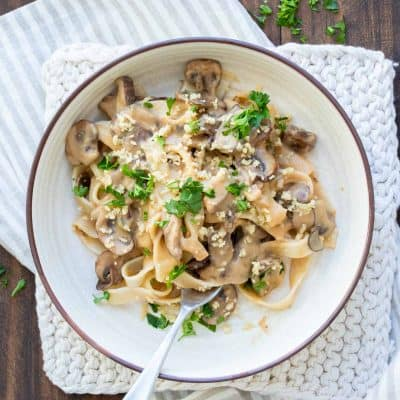 White bowl filled with fettuccini noodles and mushroom stroganoff sauce