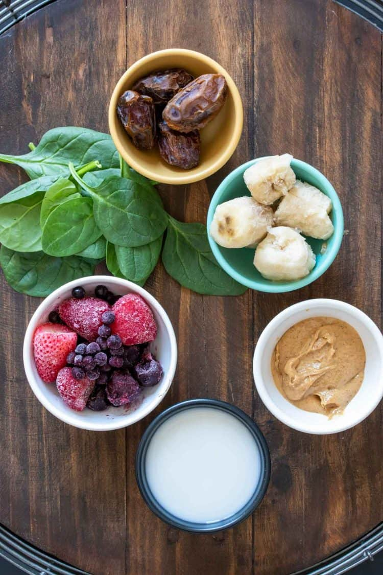 Bowls with ingredients to make a PB&J smoothie with greens