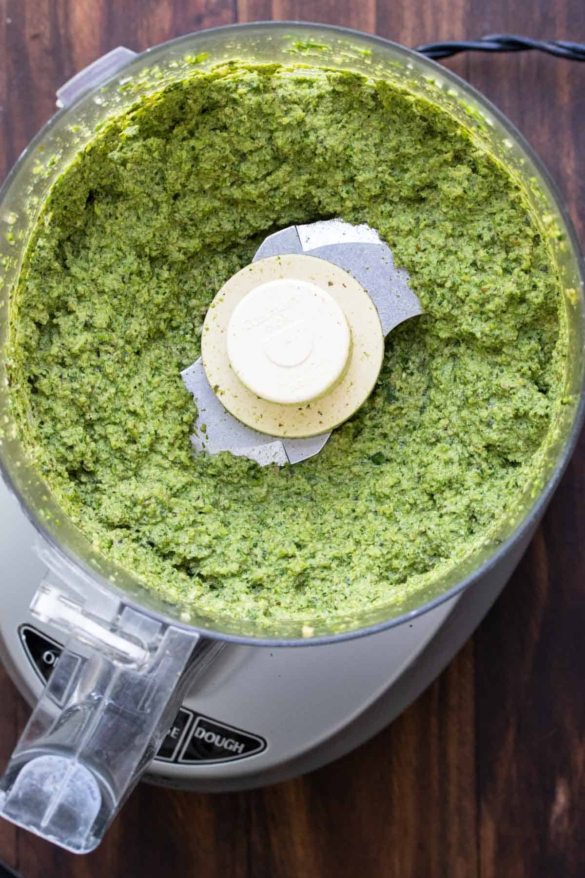 Top view of a food processor with pesto inside