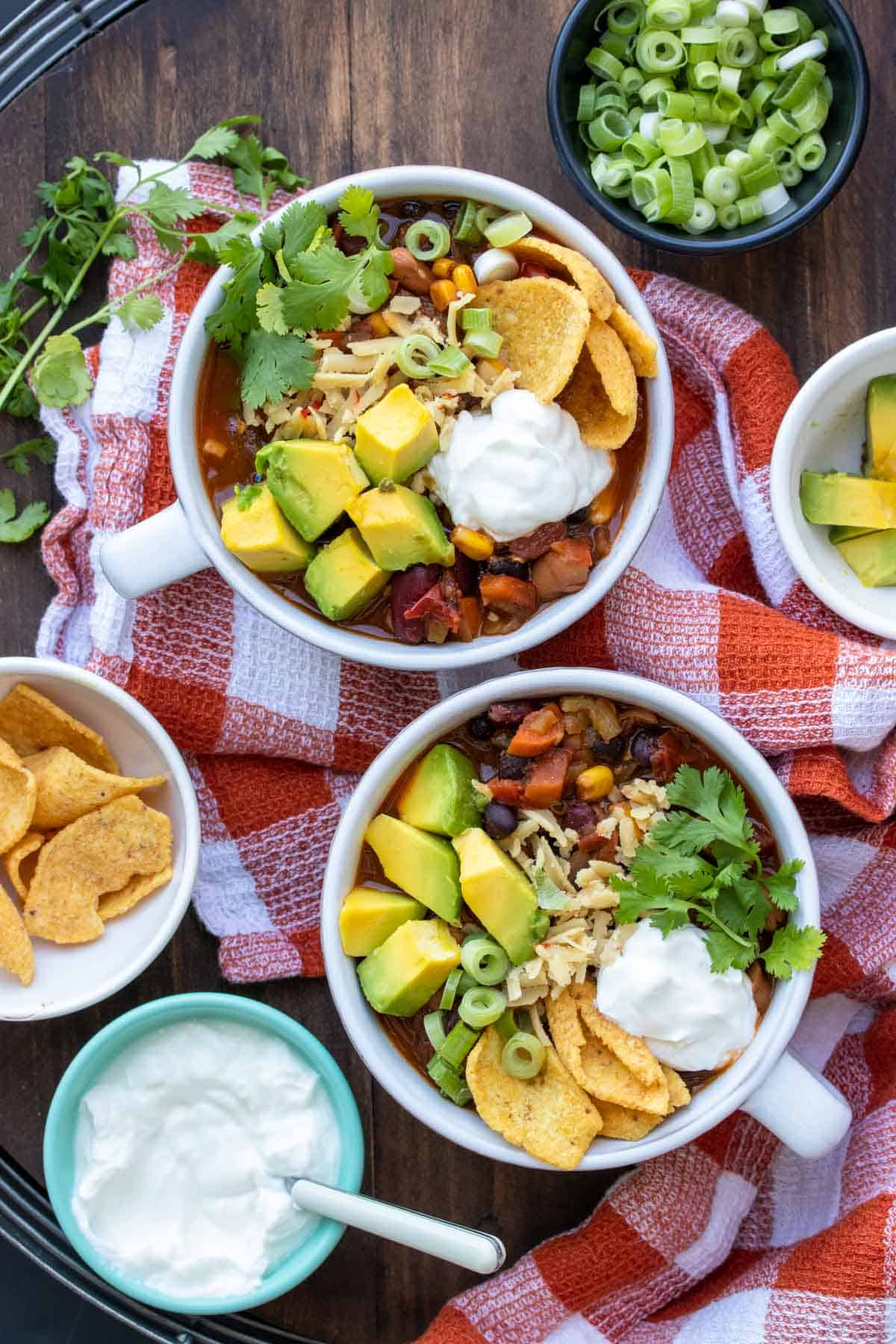 Two soup bowls filled with veggie chili surrounded by ingredients