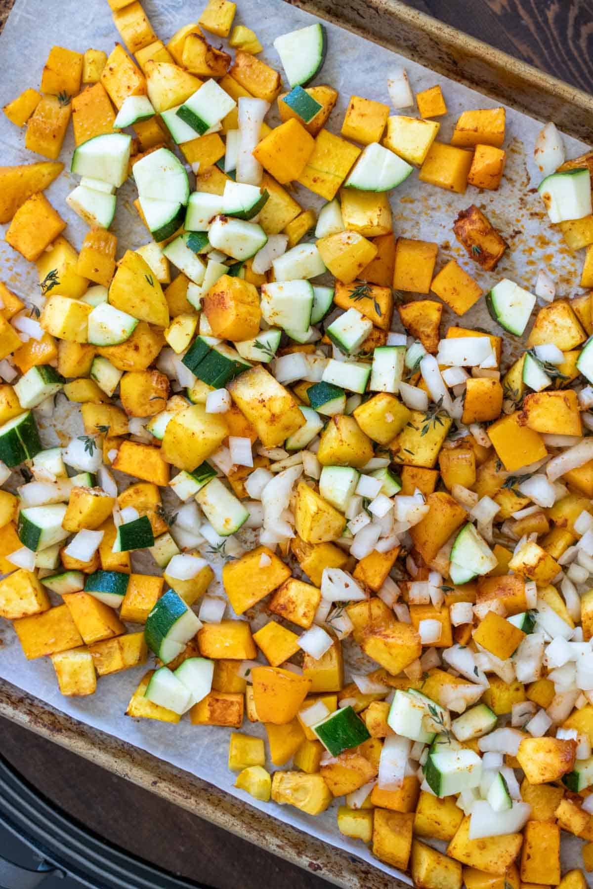 Cut pieces of zucchini and butternut squash on a baking sheet with spices