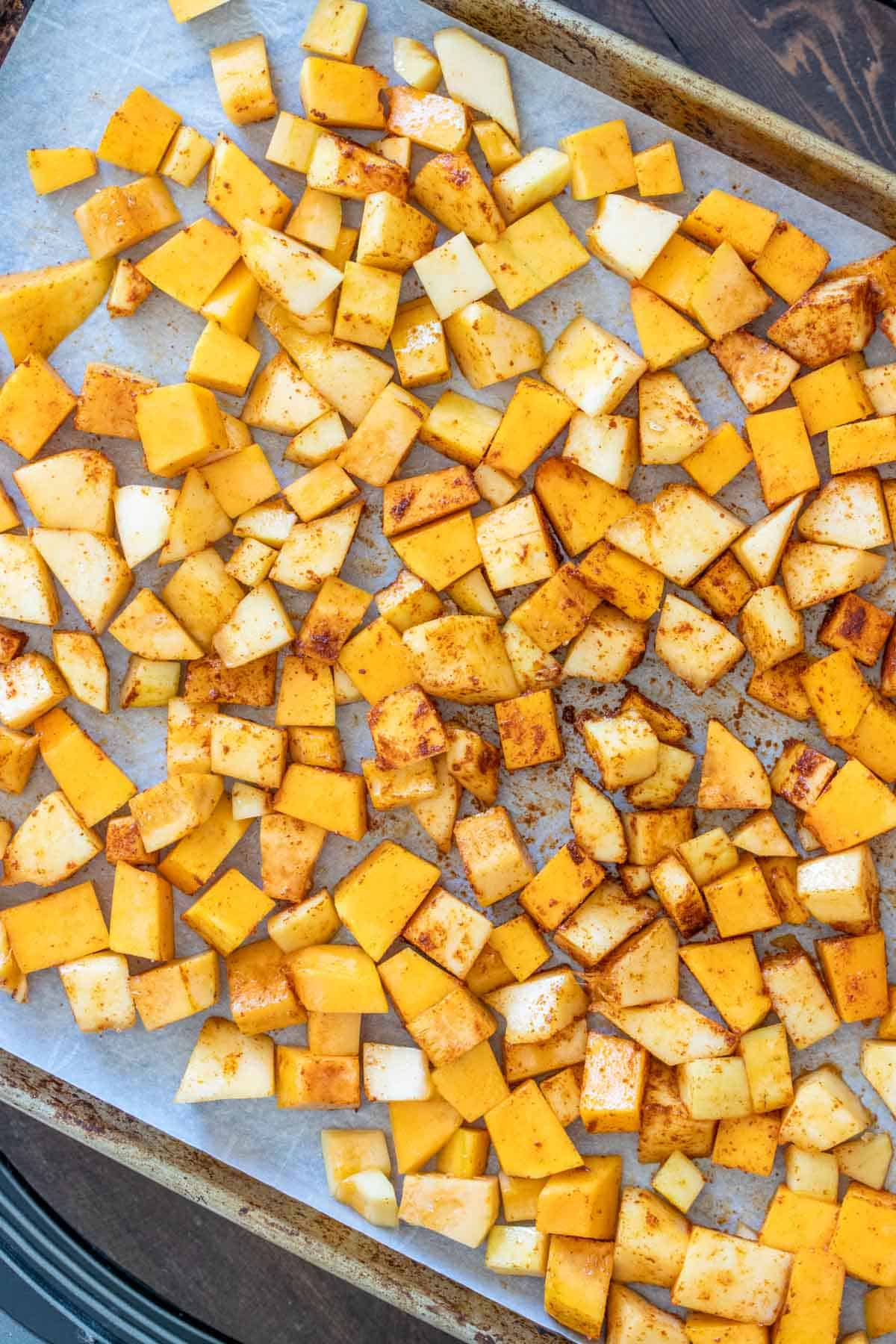 Top view of roasted butternut squash pieces on a baking sheet