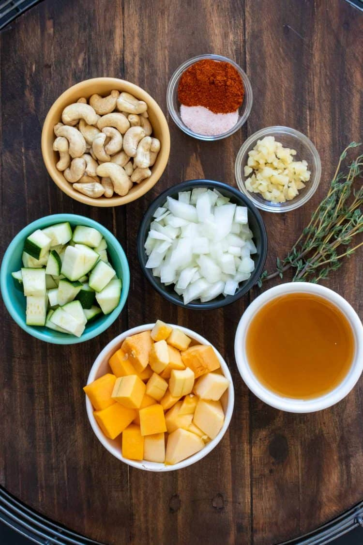 Different colored bowls filled with ingredients needed to make winter squash soup