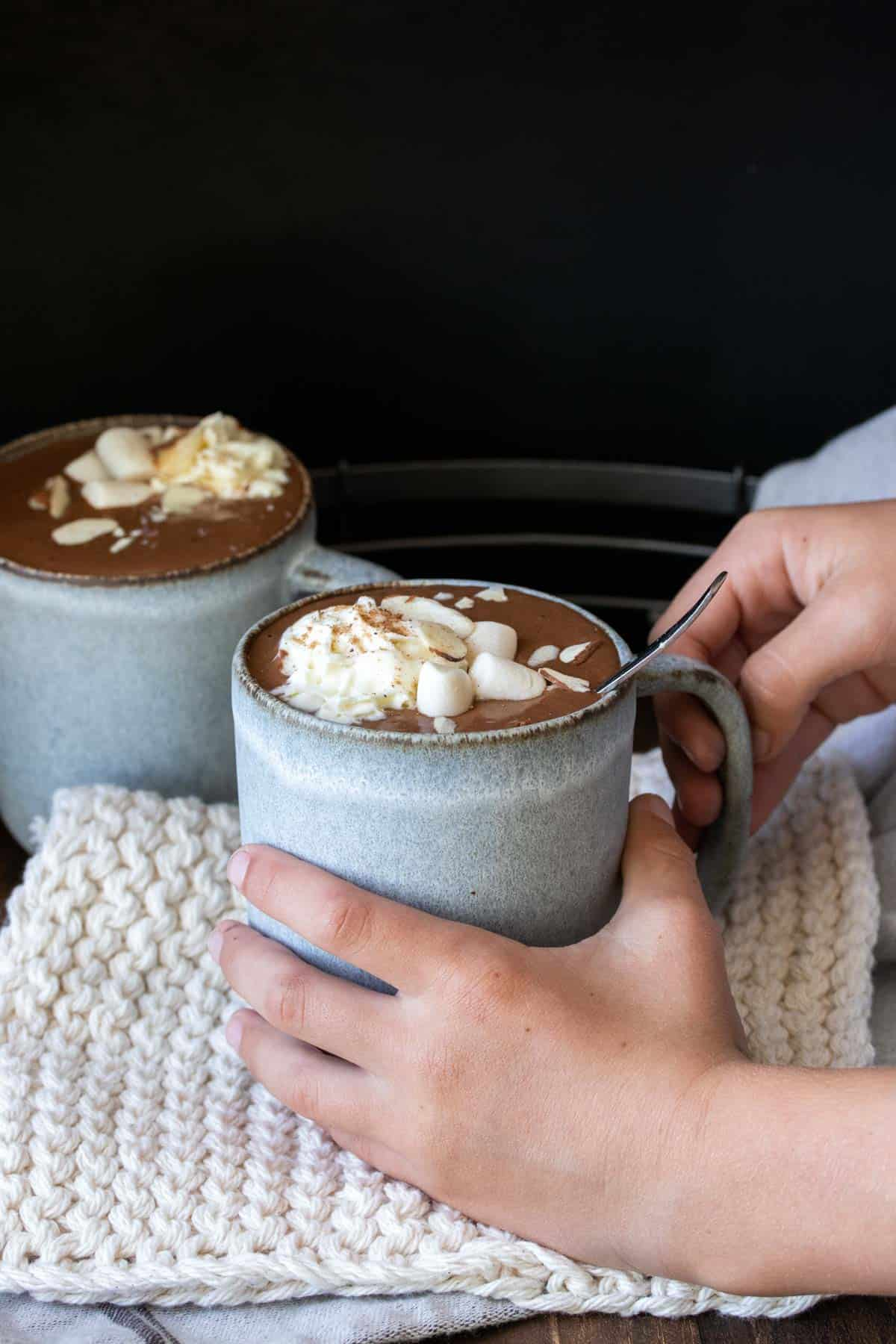 Hands grabbing a grey mug filled with hot cocoa