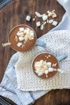Top view of two grey mugs filled with hot cocoa and topped with whipped cream and marshmallows