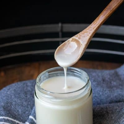 Wooden spoon taking coconut butter out of a glass jar