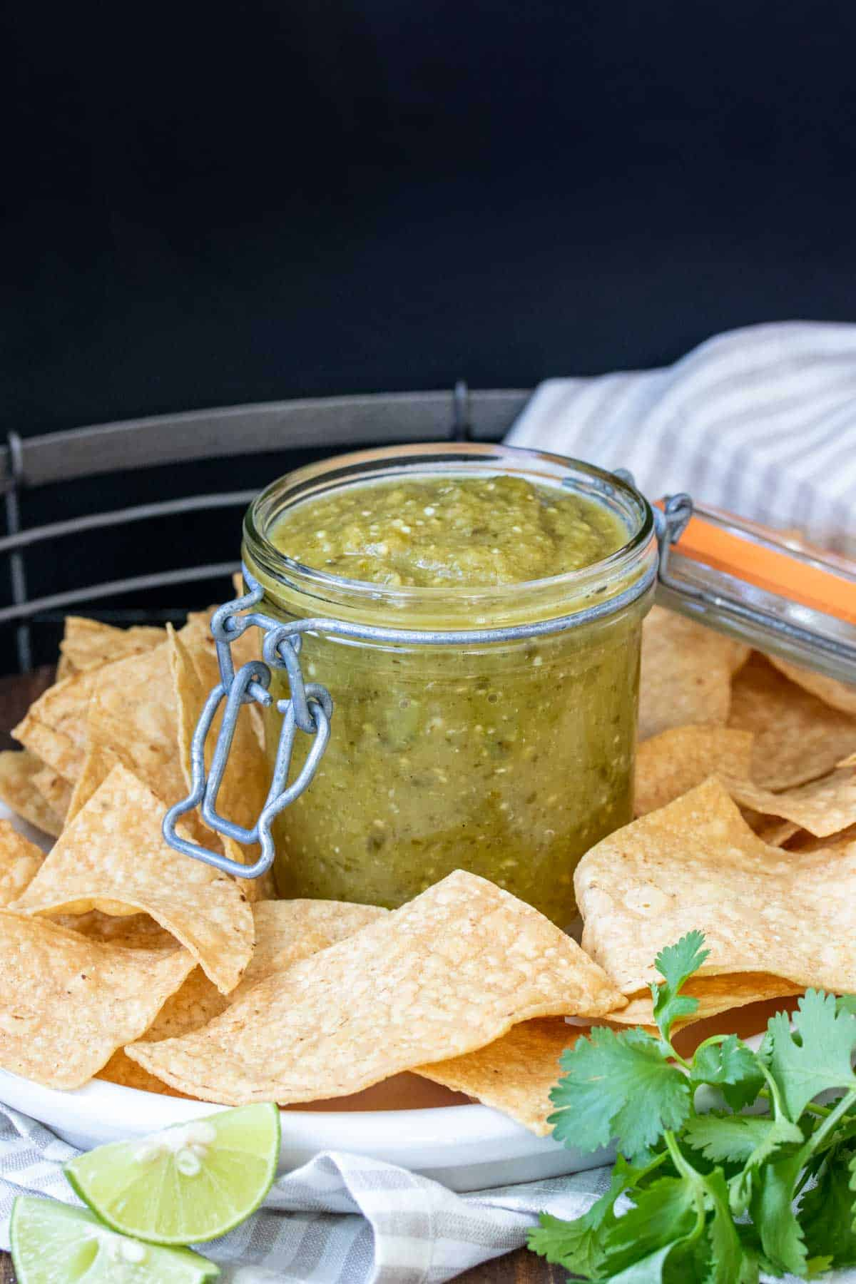 Glass jar with salsa verde sitting on a platter filled with chips