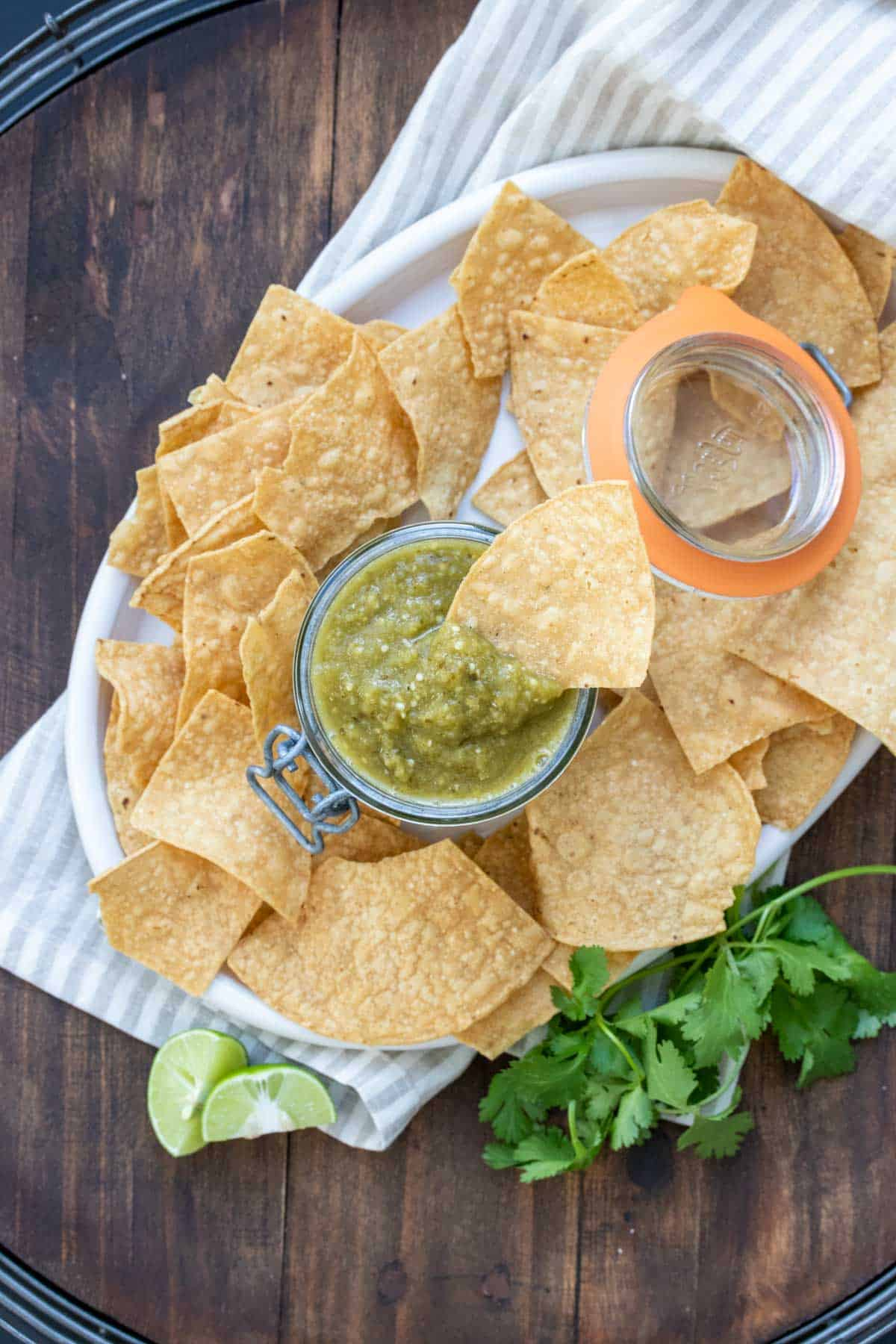 Plate with tortilla chips and a jar of salsa verde with a chip in it