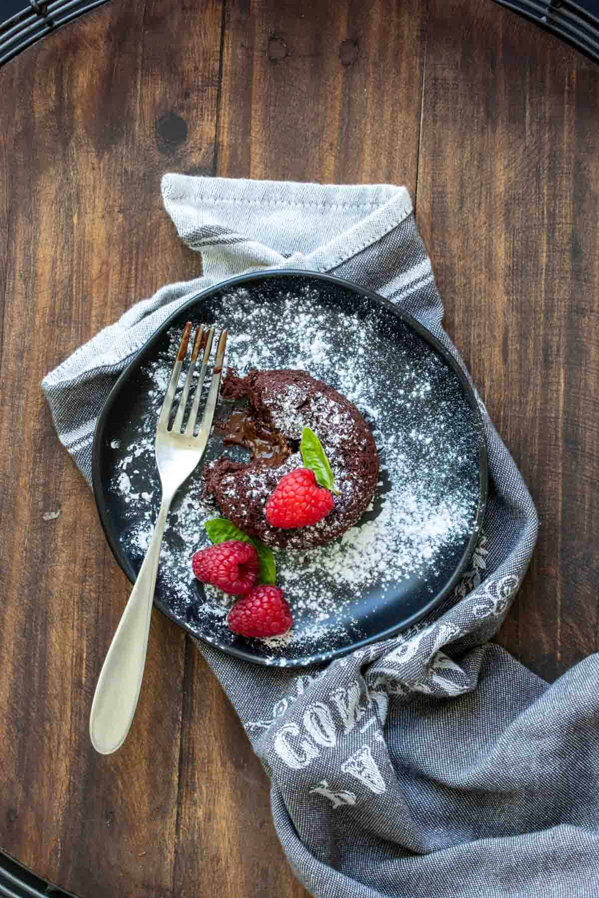 Top view of a chocolate lava cake with a bite out of it on a black plate