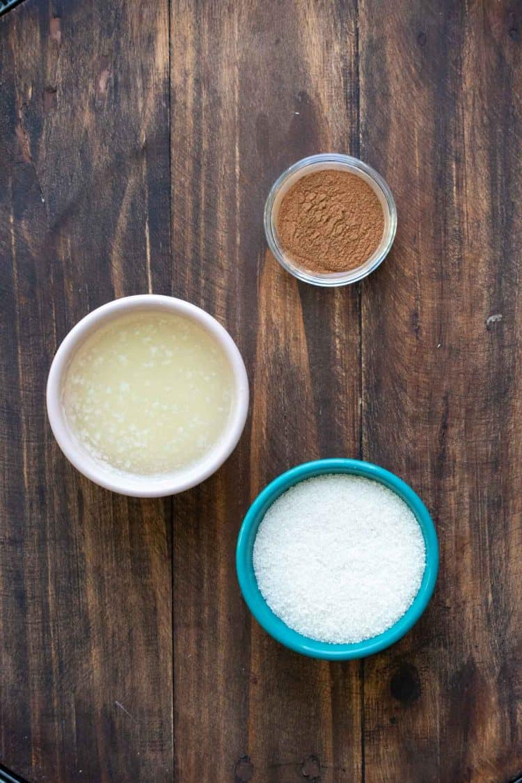 Bowls of sugar, butter and cinnamon on a wooden surface
