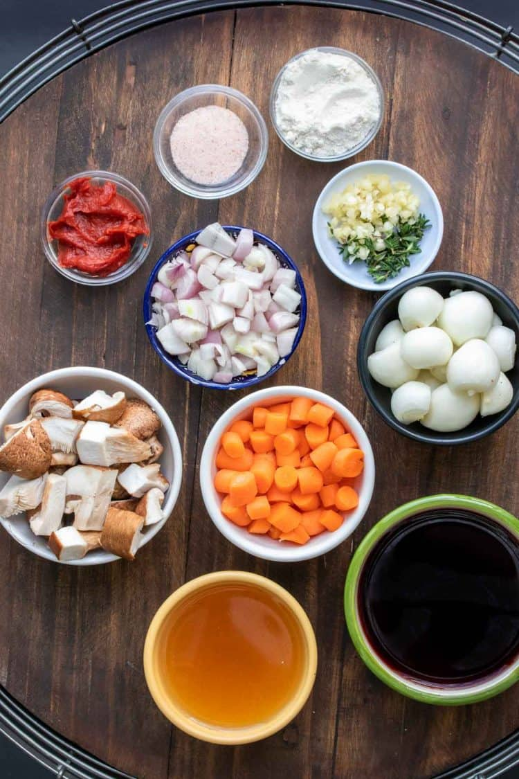 Different colored bowls on a wooden surface filled with ingredients to make mushroom bourguignon