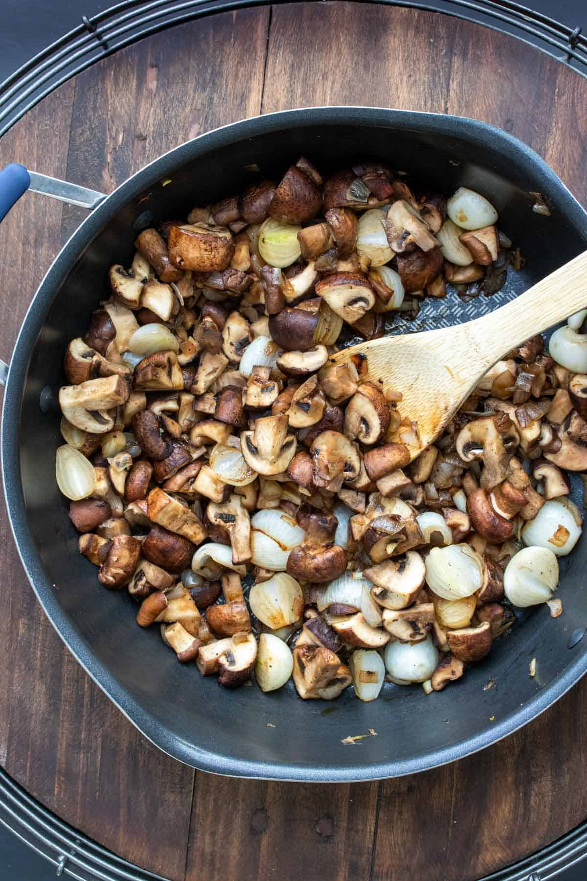 Wooden spoon mixing pearl onions and mushrooms in a pan