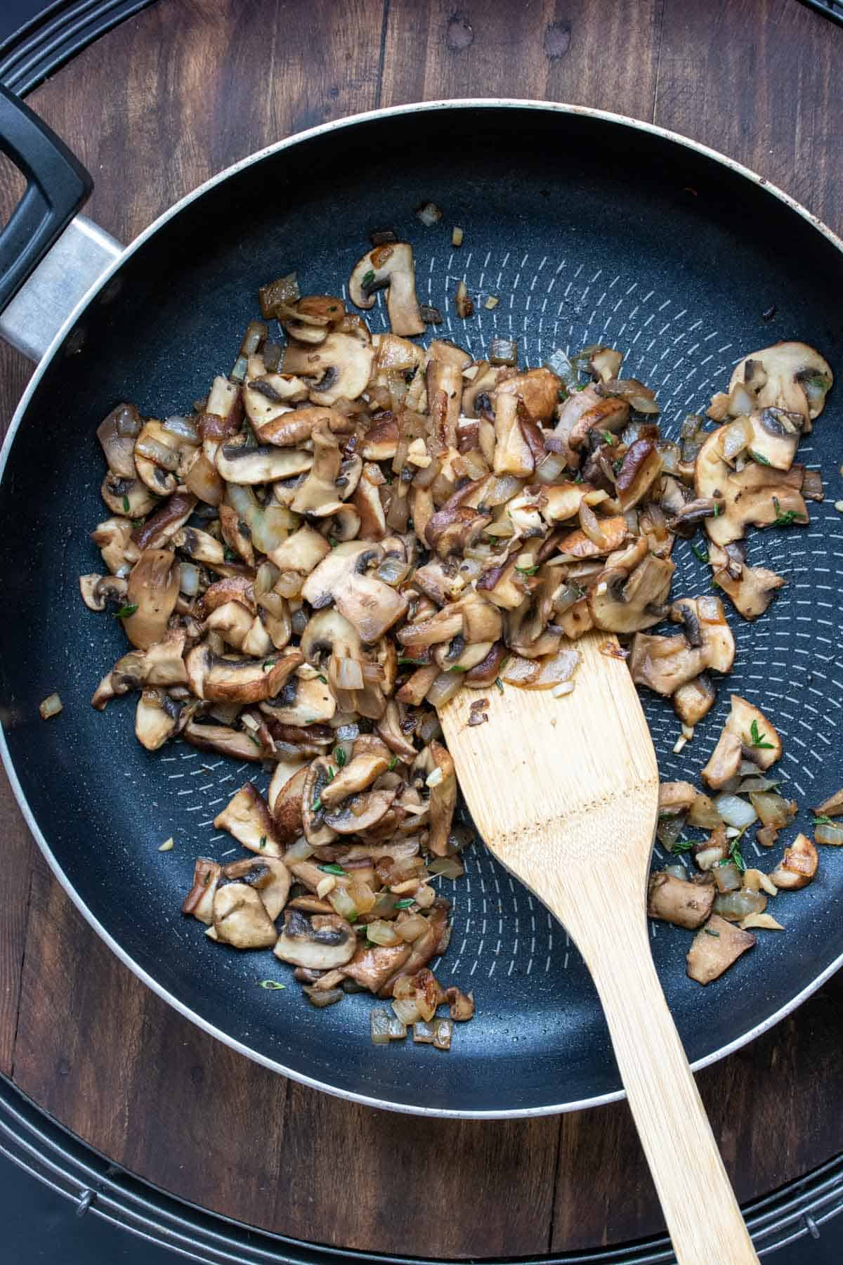 Wooden spatula mixing mushrooms in a pan to brown them
