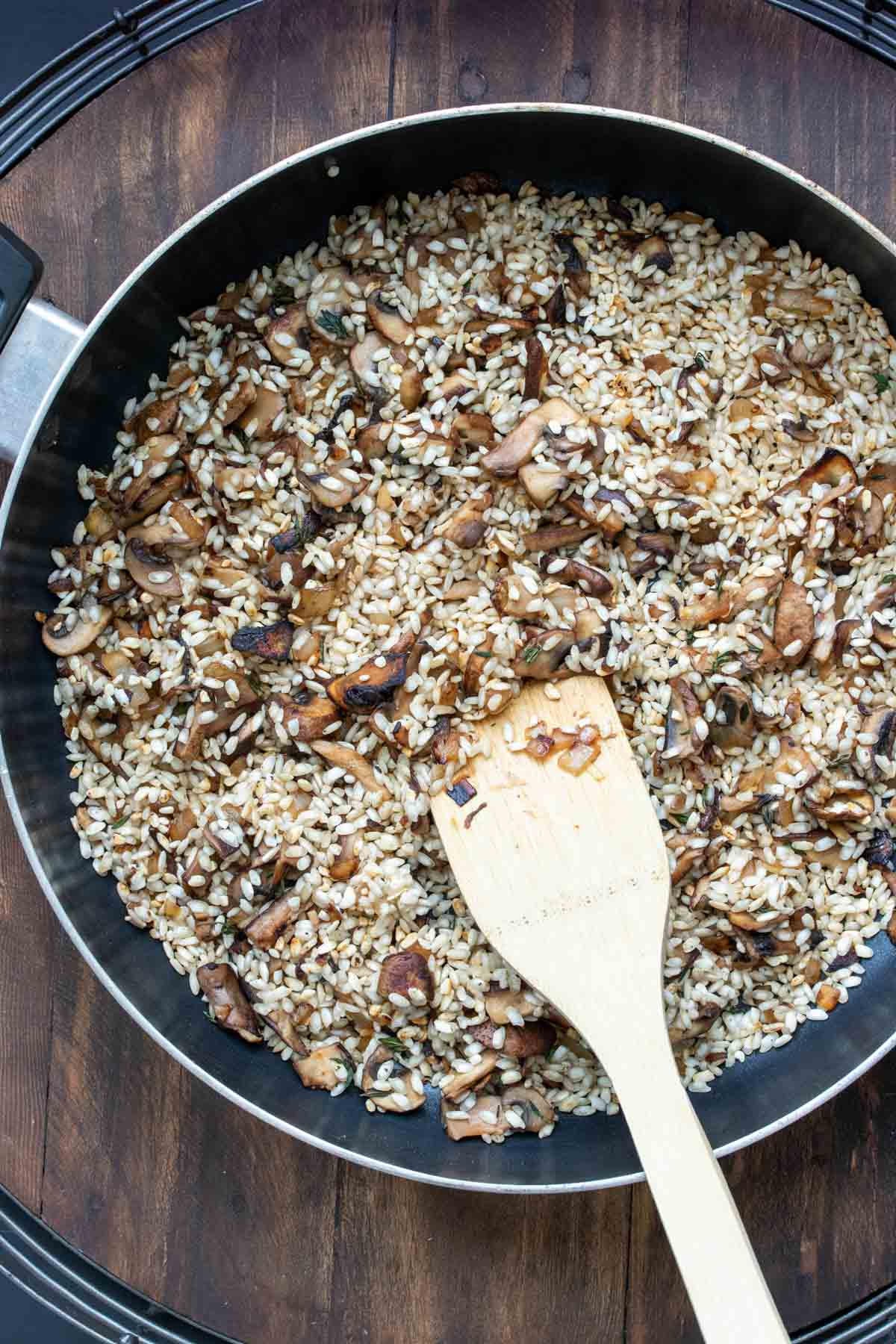Pan filled with mushrooms and uncooked rice being browned