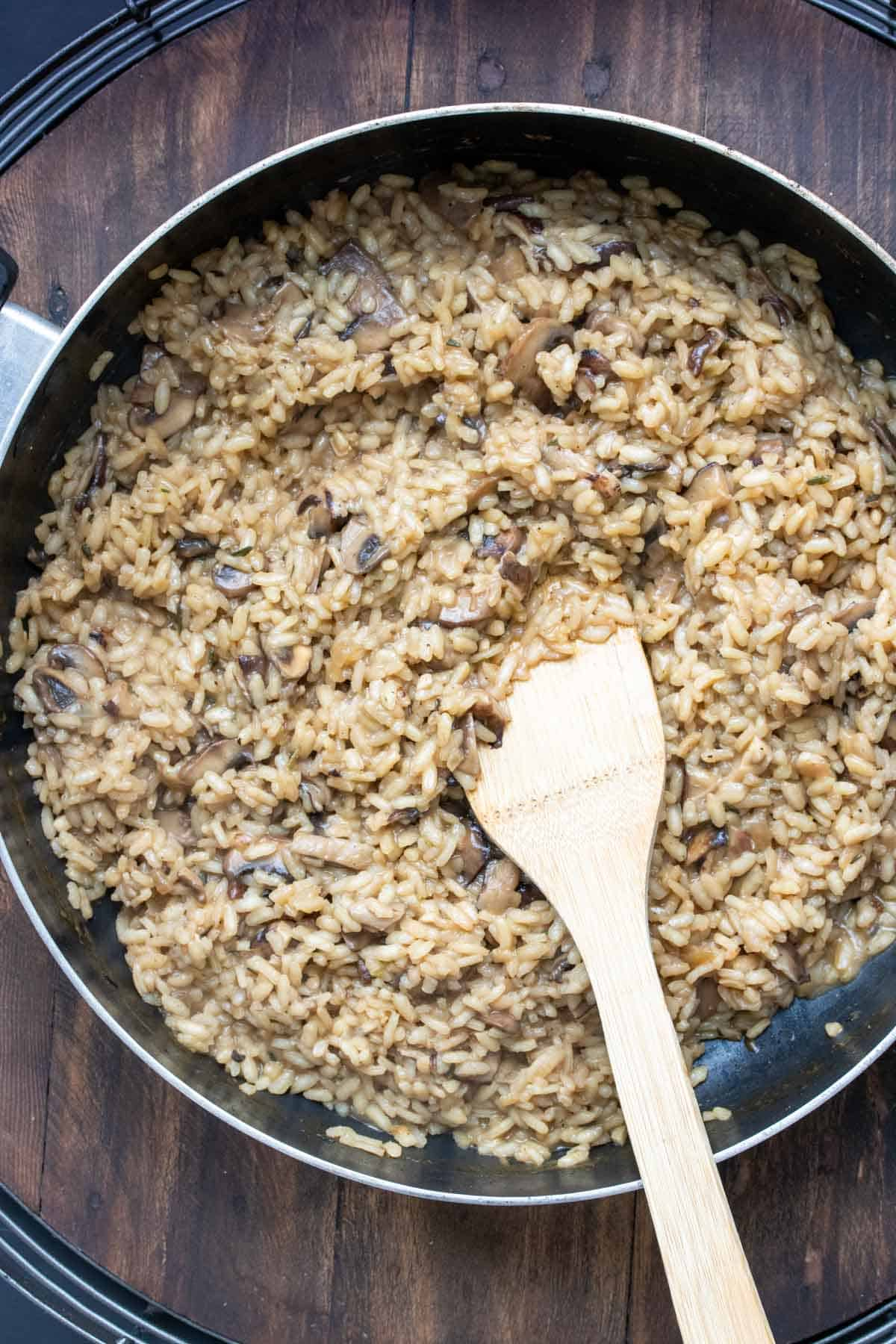 Pan with mushroom risotto cooking inside being stirred by a wooden spatula